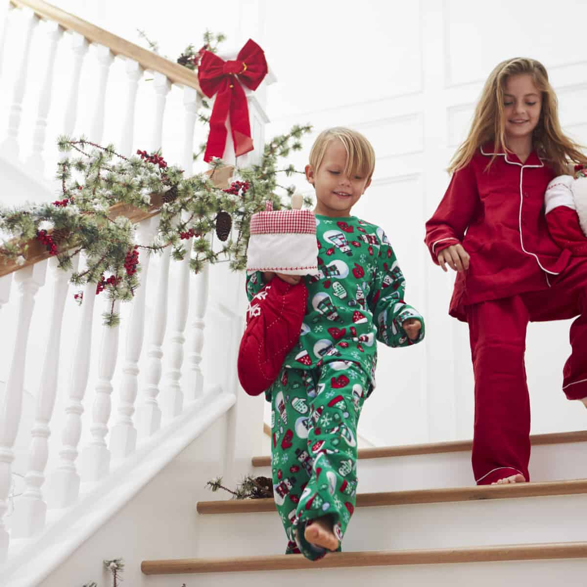 Two Children On Stairs In Pajamas With Christmas Stockings ...